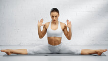 Barefoot Woman In Seated Straddle Pose On Yoga Mat.