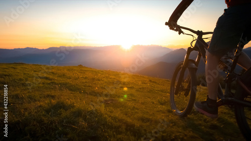 Woman riding mountain bike into the sunset. Beautiful golden summer light. - fototapety na wymiar