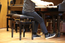 A Boy Plays The Piano While Sitting On A Chair In A Classroom At A Lesson. The Feet Of A Child In Jeans And Sneakers Press The Pedal. Image Of School Educational Process