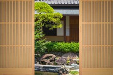 A Traditional Japanese Wooden Door Opens To A Japanese Garden