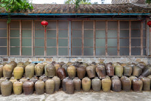 Traditional Chinese House With Stacked Rice Wine Vessels Against The Wall