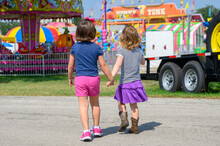 Close Up Of Two Young Girls Walking Into County Fair.