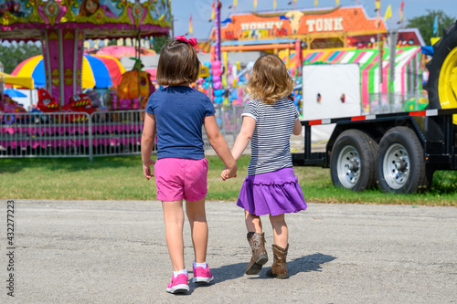 Close up of two young girls walking into county fair. Fototapet