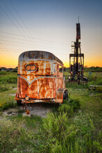 Rusty, Dilapidated Horse Trailer Next To Pump Jack.
