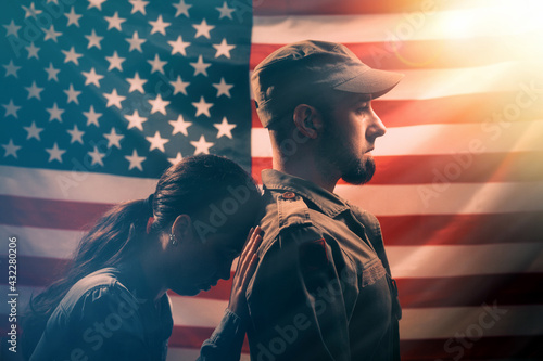 Memorial day, memorial day. The woman leans her head on the soldier's back, holding on to him with her hand. Couple on the background of the American flag. Side view. - fototapety na wymiar
