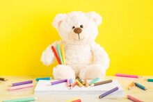 Smiling Teddy Bear, Many Colorful Pencils And Stack Of White Paper Sheets On Table At Bright Yellow Wall Background. Closeup. Front View. Drawing Concept Of Little Kids.
