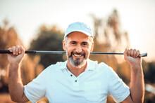 Portrait Of Senior Golfer Standing On Court.