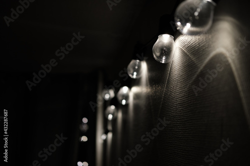 Fotografia guirlande d'ampoule allumé sur un mur blanc, lumière