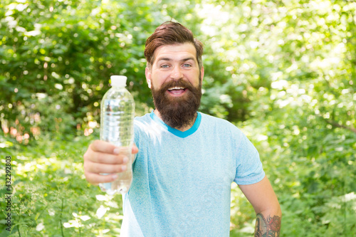 happy bearded man in summer clothes offering water bottle in forest, selective focus, per day - fototapety na wymiar