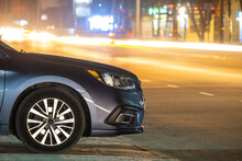 Close Up Of Parked Car On Roadside At Night With Blurred View Of Traffic Lights Of Moving Vehicles On City Street.