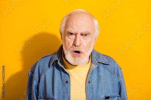 Fototapeta Portrait of unsatisfied aged man grimace face open mouth shout isolated on yellow color background obraz