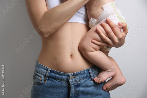 Mother with bare belly holding her baby on light grey background, closeup - fototapety na wymiar
