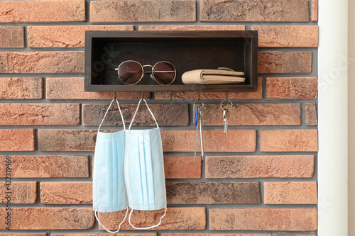 Hanger for keys with protective masks and accessories on brick wall - fototapety na wymiar