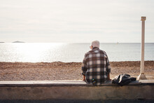 Un Retraité Assis De Dos Au Bord De La Mer. Un Homme âgé Se Reposant à La Plage. Un Vieil Homme à La Plage. Des Vacances à La Mer Pour Un Retraité. La Vieillesse. La Solitude De La Vieillesse.