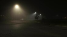 Lights Illuminate Thick Ethereal Fog On Empty City Street At Night