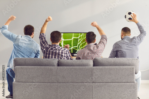 Sofa experts. Back view of male friends gathered at home to watch a football match sitting on the couch in front of the big screen TV. Men actively support their favorite team and comment on the match - fototapety na wymiar