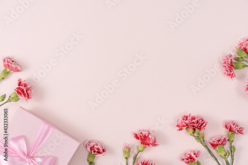 Fototapeta Mother's day background. Top view of gift with carnation bouquet on pink table background obraz