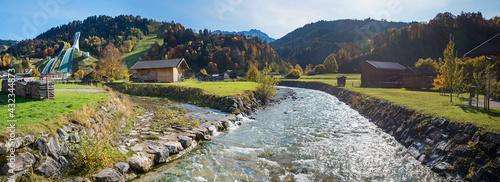Obraz na plátně Partnach river and view to famous ski jump Garmisch-Partenkirchen in autumn, pan