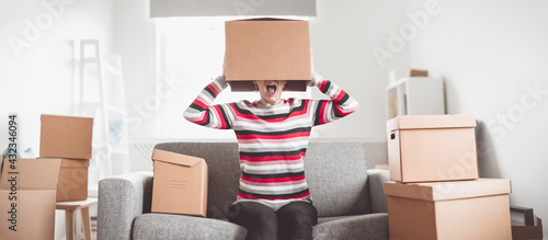 Fototapeta Tired woman with cardboard box on her head sitting on the sofa in her new house. obraz