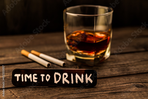 Glass of brandy with two cigarettes and the wooden plank on it is an inscription