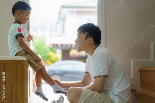 Fotomural Asian father is wearing socks for his son, fathers interact with their children throughout the day