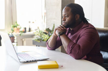 Focused And Concerned Black Man In Smart Casual Shirt Looks At Laptop Screen, Serious African-American Guy Sits At The Desk Resting Chin On Hands Feels Doubts, Solving Difficult Tasks