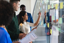Team Of Diverse Male And Female Office Colleagues Writing On Glass Board At Modern Office