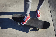 Low Section Of Caucasian Woman Standing On Skateboard In The Sun