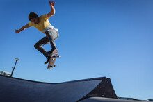 Caucasian Man Jumping And Skateboarding On Sunny Day