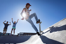 Caucasian Man Skateboarding On Sunny Day While Two Friends Cheerleading Him