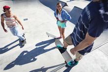 Three Happy Caucasian Female And Male Friends Skateboarding In The Sun