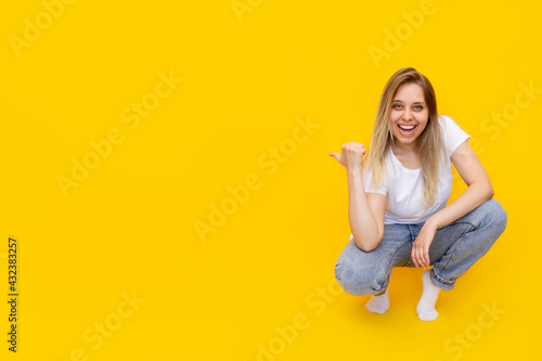 Photo A young caucasian excited smiling blonde woman sitting on her haunches, pointing