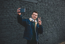 Happy Man Taking Selfie On Smartphone With V Sigh On Street