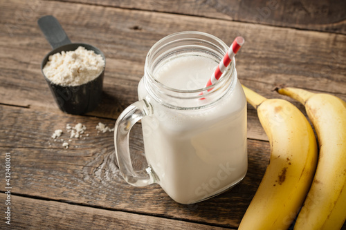 Fotografia Whey protein cocktail and banana fruit on wooden table