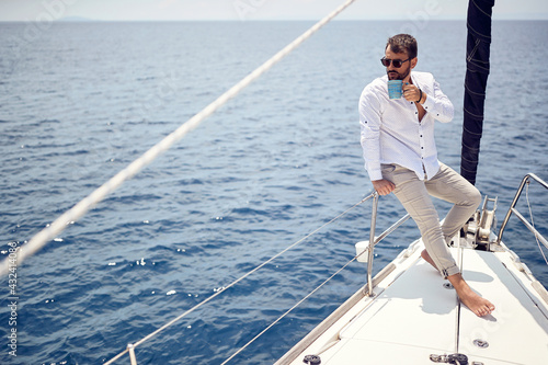 A young handsome barefoot male model is enjoying the view at a photo shooting on a yacht on the seaside. Summer, sea, vacation #432414086