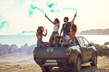 A Group Of Cheerful Friends Is Having A Good Time In The Back Of A Car By The Sea While Holding Smoke Bombs And Enjoying The Music. Summer, Sea, Vacation, Friendship