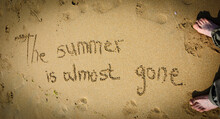 A Sentence Written On The Sand Of A Beach: THE SUMMER IS ALMOST GONE, Footprints And Female Feet . Vacation End / Back From Holiday / Back To The Work Or School Concept. Vignette Effect.