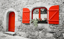 Old Stone House With Red Wooden Shutters And Red Door. Boxes With Red And White Flowers On The Window. Brittany, France. Retro Aged Black White Photo.