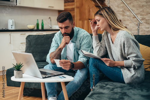 Obraz Young worried couple using a laptop for calculating their monthly budget - fototapety do salonu