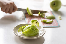 Bird From Apple Slices On The Background Of A Man Cutting A Green Apple On A Chopping Board