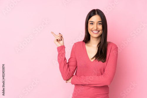Young caucasian woman over isolated background happy and pointing up Fototapet
