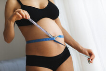 Pregnant Woman Measure Her Belly With Measure Tape.
