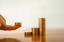 Business , Financial And Saving Concept. Closeup Of Stack Of Gold Coins With Stack Of Coins On Finger.