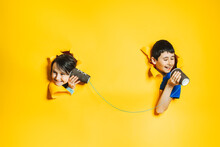 A Little Girl And Boy Playing With A Handmade Toy Phone With A Paper Cup And Thread. Children Look Into Holes In Torn Yellow Background. Communication Technology, Information Transfer Concept.