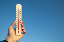 Hand Holding Thermometer On Blue Sky Background.