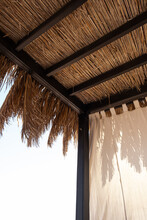 Beautiful Lounge Pavilion Canopy For Relax On The Beach With Sea Side View And Blue Sky. Tent Made Of Dry Palm Leaves. Luxury Summer Vacation In Tropical Paradise Resort Hotel