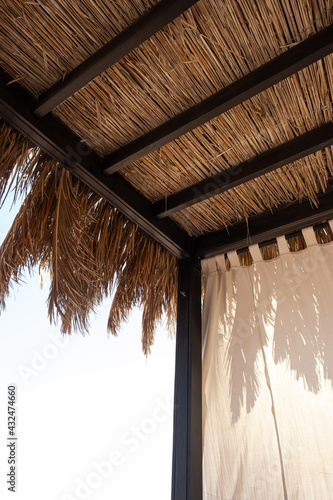 Fototapeta Beautiful lounge pavilion canopy for relax on the beach with sea side view and blue sky. Tent made of dry palm leaves. Luxury summer vacation in tropical paradise resort hotel obraz