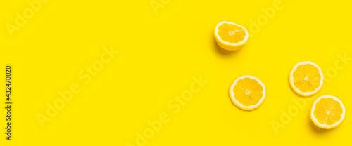 Photo lemon wedges and sliced lemon on a yellow background