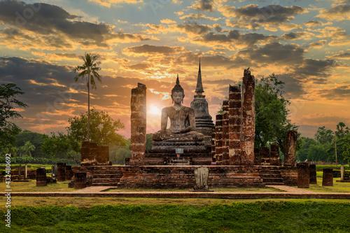 Buddha statue and pagoda Wat Mahathat temple with dramatic syk sunset, Sukhothai Fototapeta