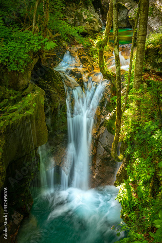 Beautiful water cascades or small waterfall in the valley of Lepena in Slovenian Julian Alps. Emerald green waterfalls in an enchanted forest. Wall mural